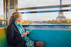 Beautiful young woman travelling in a train of Parisian underground and using her mobile phone royalty free stock photography