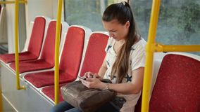 Beautiful young woman travelling in urban transport and using her mobile phone. Female using smartphone in public stock video