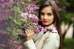 Beautiful young woman in a trench coat near blooming lilac. Fashion beauty portrait Stock Images