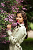 Beautiful young woman in a trench coat near blooming lilac. Fashion beauty portrait Stock Photo