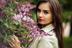 Beautiful young woman in a trench coat near blooming lilac. Fashion beauty portrait Stock Image