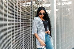 Beautiful young woman in trendy stylish clothes with vintage. Sunglasses near the grid stock images