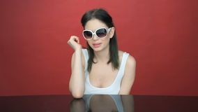 Beautiful young woman in trendy sunglasses. Sitting at a table smiling at the camera stock footage