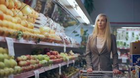 Beautiful young woman with trolley shopping in supermarket.  stock video footage