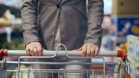 Beautiful young woman with trolley walking in supermarket.  stock footage