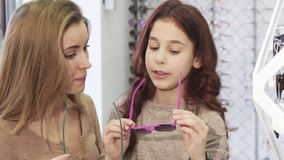 Beautiful young woman trying on sunglasses with her cute little sister stock video