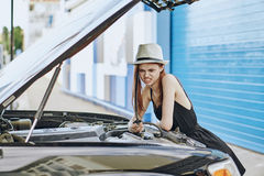 Beautiful young woman trying to mend a car outdoors in the city Stock Photography