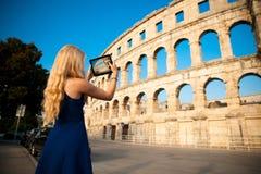 Beautiful young woman turist taking photos of roman arena in Pula croatia royalty free stock photography