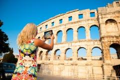Beautiful young woman turist taking photos of roman arena in Pul. A croatia Stock Photos
