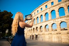 Beautiful young woman turist taking photos of roman arena in Pul. A croatia Royalty Free Stock Image