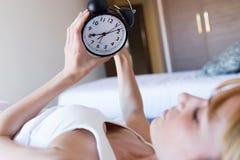 Beautiful young woman turning off the alarm clock imágenes de archivo libres de regalías