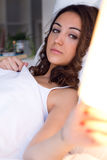 Beautiful young woman turning off the lamp. Royalty Free Stock Photography