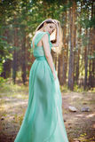 Beautiful young woman in a turquoise dress in a pine forest royalty free stock photography