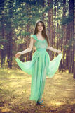 Beautiful young woman in a turquoise dress in a pine forest Stock Photo