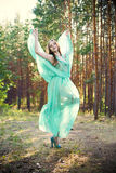Beautiful young woman in a turquoise dress in a pine forest Stock Image