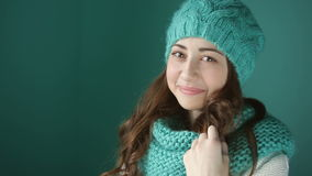 Beautiful young woman in a turquoise knitted hat and scarf stock video