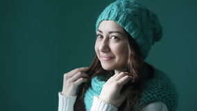 Beautiful young woman in a turquoise knitted hat and scarf.  stock footage