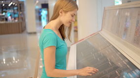 Beautiful young woman in turquoise t-shirt in mall. Looking for a particular store on mall layout. Beautiful young woman in turquoise t-shirt in mall. Looking stock video footage