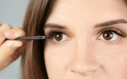 Beautiful young woman with tweezers. And artificial eyelashes on light background Royalty Free Stock Photography