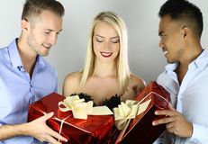 Beautiful young woman with two boyfriends giving presents. Beautiful young women with two boyfriends giving presents on a white background royalty free stock photo