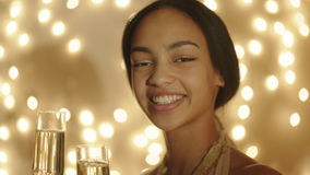 Beautiful young woman with two champagne glasses in her hands. Close up shot of beautiful young woman with two champagne glasses in her hands. Bokeh lights on stock video