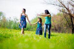 Beautiful Young Woman with Two Children in the park. Happy family outdoors. women and two children having fun.Summer. Mother and daughter in the park. Happy Stock Photo