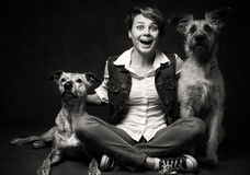 Beautiful young woman with two funny dogs on a dark background. Stock Photos