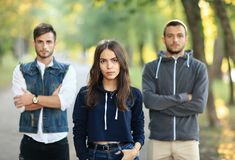 Beautiful young woman and two men behind her. Beautiful young women and two men with arms crossed behind her. Half body portrait of three people on nature. Girl Royalty Free Stock Images