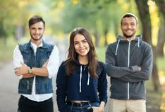 Beautiful young woman and two men behind her. Beautiful young women and two men with arms crossed behind her. Half body portrait of three people on nature. Girl Stock Photo