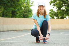 Beautiful young woman tying her laces before a run. Royalty Free Stock Images
