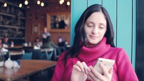 Beautiful young woman type message on mobile phone stock footage