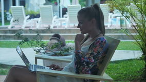 Beautiful young woman typing on laptop, outdoor. stock video