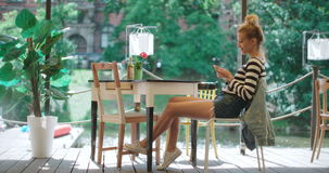 Beautiful young woman typing on phone in a cafe. Young caucasian woman typing on phone during sunny day, outdoors stock video footage