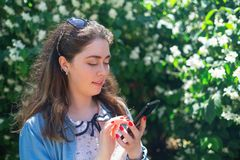 Beautiful young woman typing on phone. Plants in the background. Copy space. Concept of modern technology and internet.  stock photography
