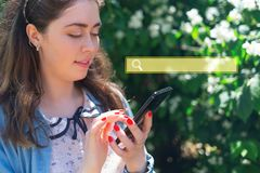 Beautiful young woman typing on phone. Plants in the background. Copy space. Sign of searching. Concept of modern technology and. Beautiful young woman typing on stock photography
