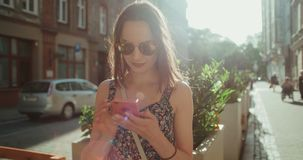 Beautiful young woman typing on phone during sunny day. Young brunette girl enjoying sunny day and using phone, outdoors stock video footage