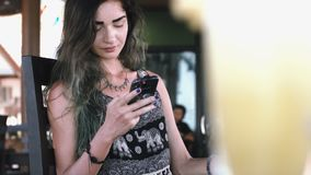 Beautiful young woman typing on phone during sunny day in a cafe on the street. stock video footage