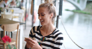 Beautiful young woman typing on phone during sunny day in an outdoors cafe. Stock Images
