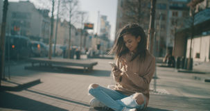 Beautiful young woman typing on phone during sunny day. Royalty Free Stock Photography