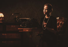 Beautiful young woman typing in retro interior Stock Image
