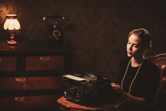 Beautiful young woman typing in retro interior Royalty Free Stock Image