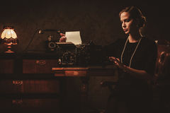 Beautiful young woman typing in retro interior Royalty Free Stock Photography
