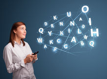 Young woman typing on smartphone with high tech 3d letters commi Stock Images