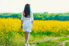 Beautiful young woman in Ukrainian embroidered standing in a field of yellow rape flowers Stock Photo
