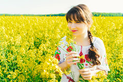 Beautiful young woman in Ukrainian embroidered standing in a field of yellow flowers Royalty Free Stock Images