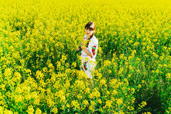 Beautiful young woman in Ukrainian embroidered standing in a field of yellow flowers Stock Image