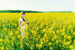 Beautiful young woman in Ukrainian embroidered standing in a field of yellow flowers Stock Images