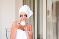 Beautiful young woman with under eye patches in bathrobe holding cup of coffee and drink drinking . Happy girl relax in hotel royalty free stock images