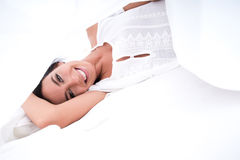 A beautiful young woman under the sheets in the bed Stock Image