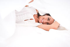 A beautiful young woman under the sheets in the bed Stock Photo